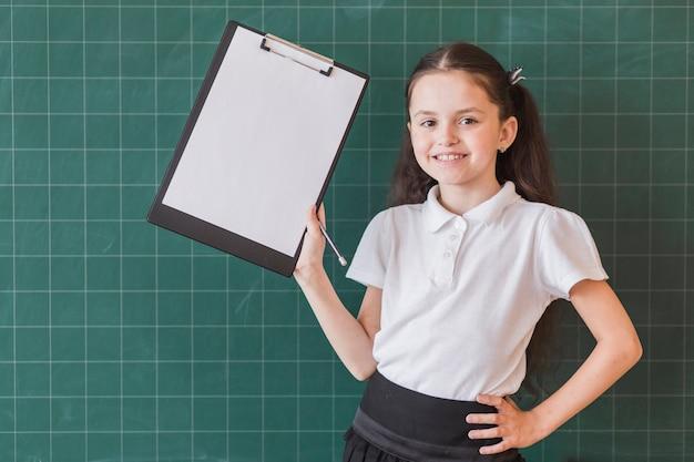 Girl with file holder near blackboard