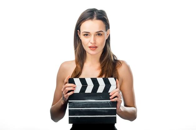 흰색 배경에 서 있는 영화 분자와 소녀입니다. 아름다움의 손에 클래퍼 보드입니다.