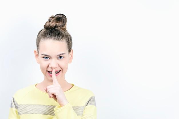 입에 손가락이 달린 소녀와 브래킷이 설치되었습니다.