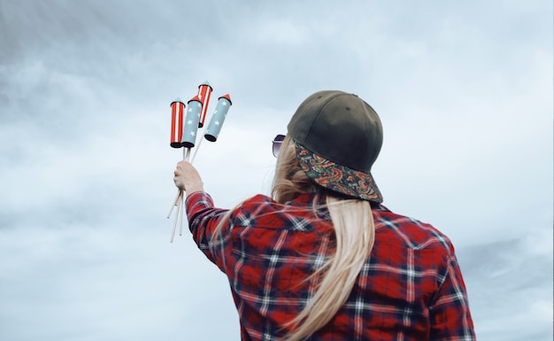 A girl with fireworks in her hands, is preparing to launch missiles in honor of the independence day celebration on july 4