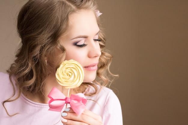 花のマシュマロを持つ少女。