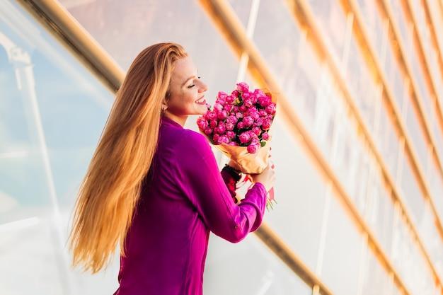 モダンな建物の近くの花と長い髪の少女