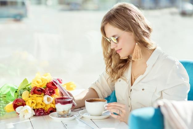花、コーヒー、ヨーグルト、カフェで電話を持つ女の子