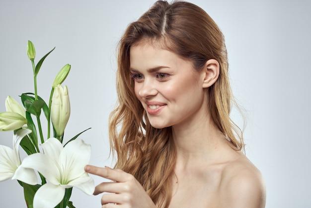 花のクロップドビューポートレートクローズアップ春の裸の肩の透明な肌を持つ少女メイクアップ