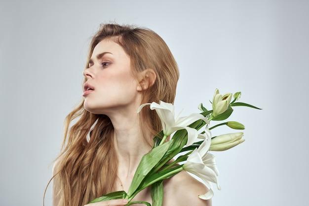 Девушка с цветами обрезанный вид портрет крупным планом весенние голые плечи чистая кожа макияж.