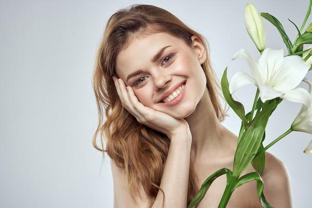 花のトリミングされたビューの肖像画のクローズアップ春の裸の肩の透明な肌を持つ少女