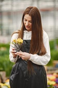 温室で花を持つ少女。エプロンの庭師。フラワーケア。