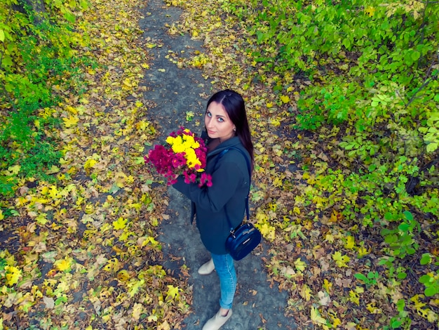 Girl with flowers walks in the autumn forest
