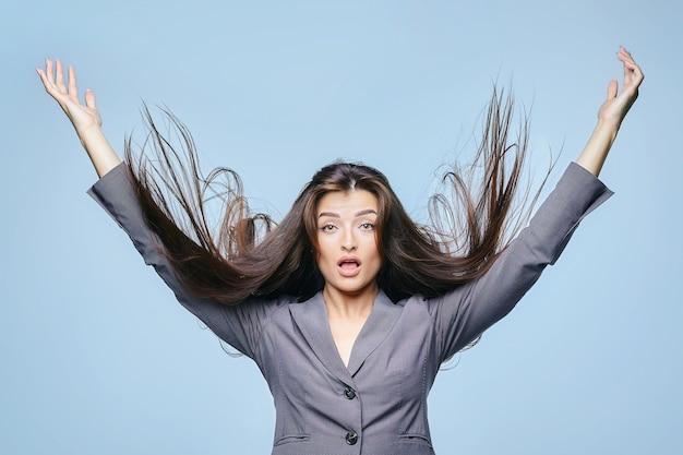 飛んでいる髪の少女が青い背景のスタジオでポーズをとる