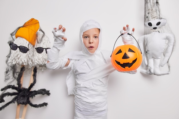 Girl with freckles dressed in halloween costume holds carved pumpkin poses around frightening toys creepy creatures on white