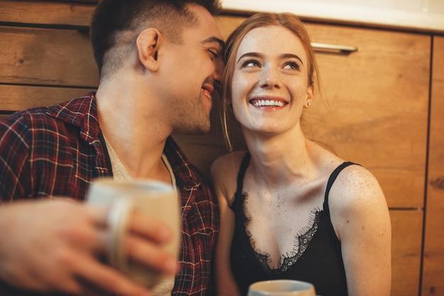 Девушка с веснушками пьет кофе на причале