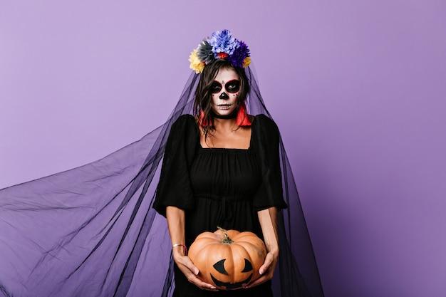 ハロウィーンの肖像画のためにカボチャでポーズをとって、恐ろしいメイクの女の子。