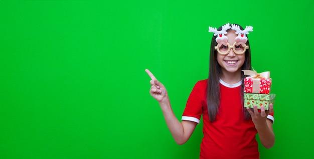 재미있는 안경을 쓴 소녀는 광고 공간을 가리키는 손에 크리스마스 새해 선물을 들고 있다