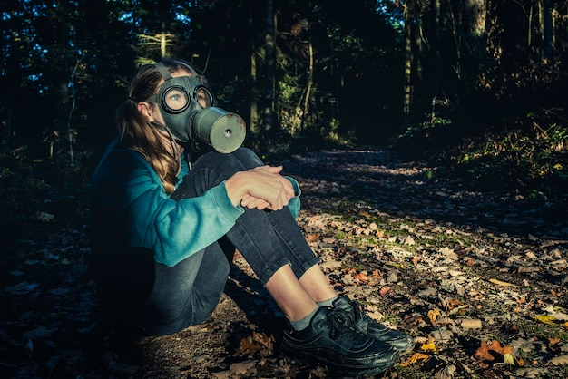 Девушка с противогазом в лесу на закате
