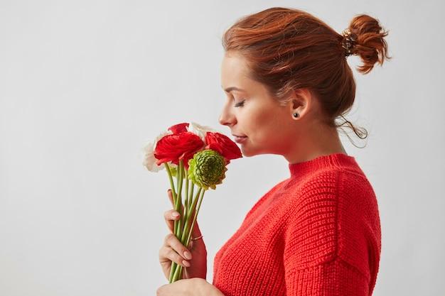 흰색 배경에 장미 꽃다발을 얹은 빨간 스웨터에 머리를 모은 소녀가 문자를 보낼 수 있는 프로필에 서 있습니다.