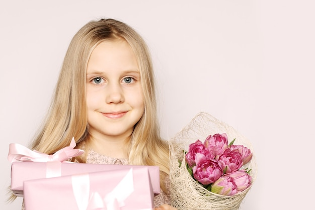Girl with gift box and flowers
