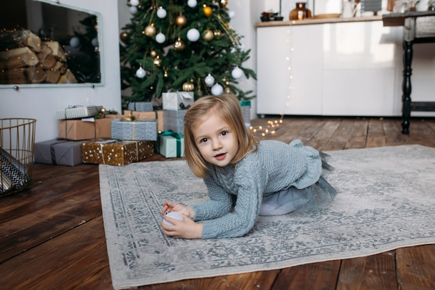 Girl with gift boxes and christmas tree on background
