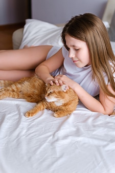A girl with a ginger cat lies on a white bed. a young girl is stroking a ginger cat while lying on a white sheet