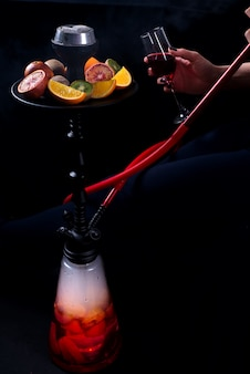 A girl with a glass of wine in her hands smokes a hookah