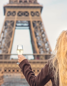 Girl with a glass of wine near the eiffel tower in paris. selective focus.