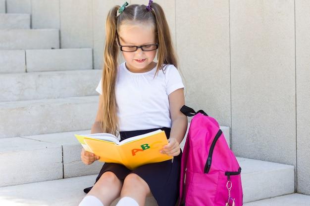 メガネと公園でバックパックを持つ少女。学校の最初の日