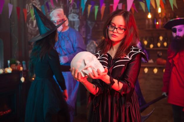 人間の頭蓋骨を見ている魔女のように着飾った眼鏡の少女背景の男は海賊のように着飾った。ハロウィーンのお祝い。