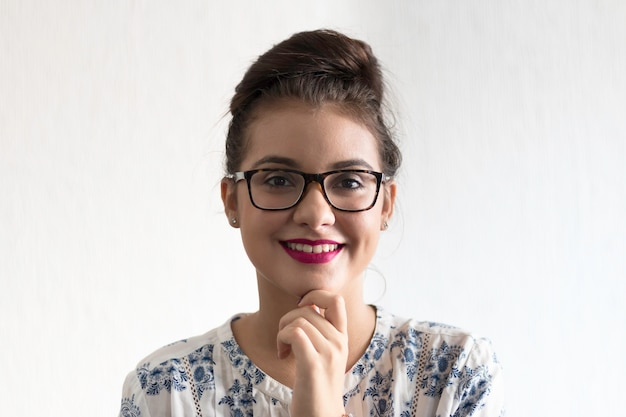 Girl with glasses and hand on chin with white background.