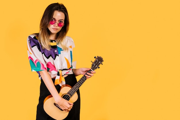 Girl with glasses playing the ukelele