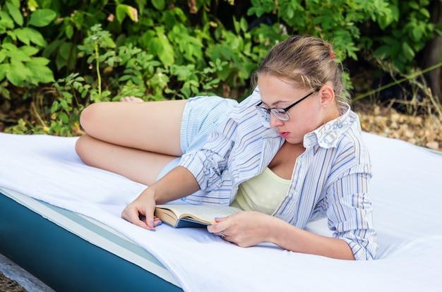 Девушка в очках читает книгу, лежа на надувном матрасе в лесу