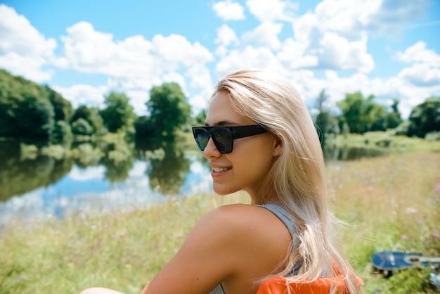 Девушка в очках сидит на природе