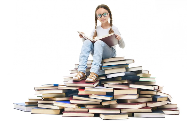 Girl with glasses sitting on a pile of books