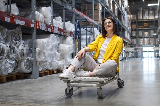 Girl with glasses sitting on a shopping cart in a store in the warehouse