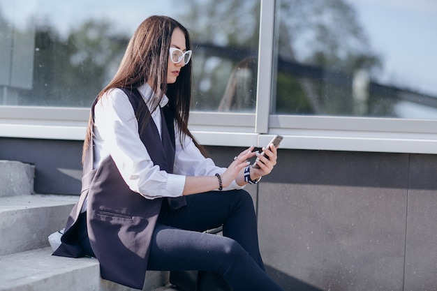 Girl with glasses sitting on stairs looking at a mobile