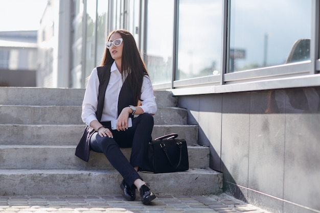 Girl with glasses sitting on stairs