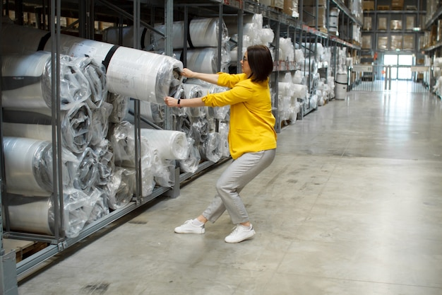 Girl with glasses takes a big and heavy mattress in the store. self-service warehouse
