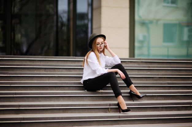 Girl with glasses and vintage hat sitting on the steps