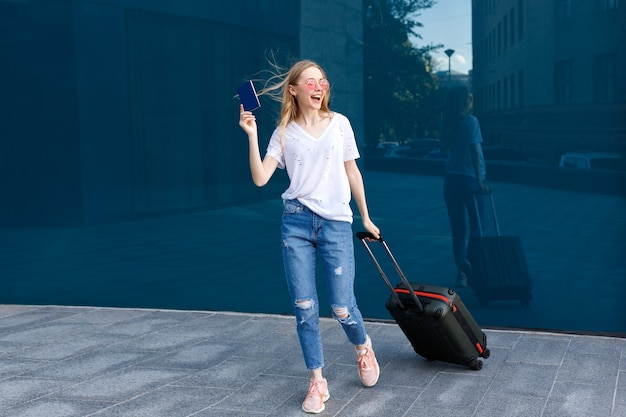 A girl with glasses with luggage and passport goes on a blue background adventure