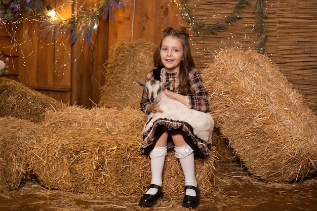 レトロなドレスを着ている干し草の背景に農場の小屋でヤギを持つ少女