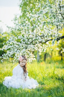 Girl with a goat sitting in the grass in a lush apple orchard