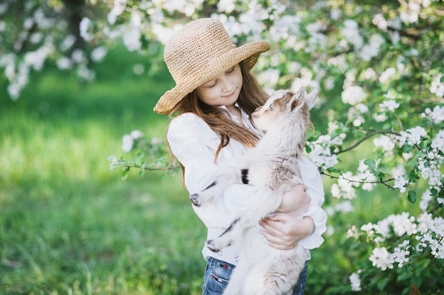 Girl with a goat standing in the grass in a lush apple orchard