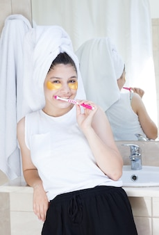 Girl with golden moisturizing patches brushes teeth in bathroom