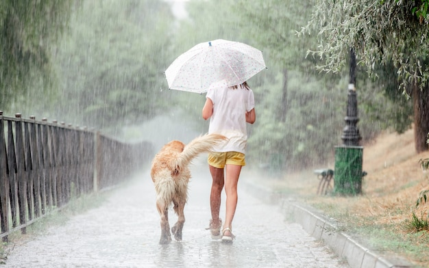 Girl with golden retriever dog during rain walking wet under umbrella outside. preteen kid with doggy pet in rainy day back portrait