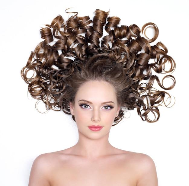 Ragazza con splendidi bei capelli ricci su bianco