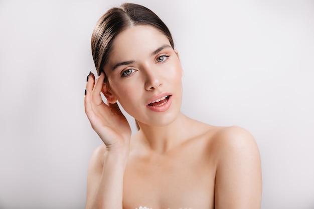 녹색 눈과 검은 머리를 가진 소녀입니다. 흰 벽에 건강한 피부를 가진 모델의 초상화.