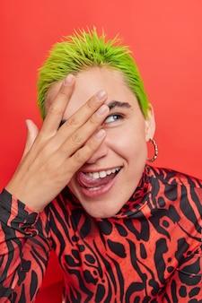 緑の髪の少女が舌を突き出して指を通して見えるfnはどこか脇に見える鮮やかな赤のカジュアルなタートルネックに身を包んだ