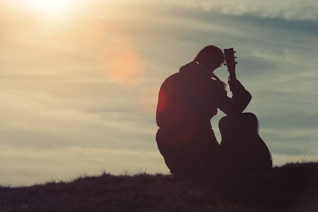 草の中のギターを持つ少女