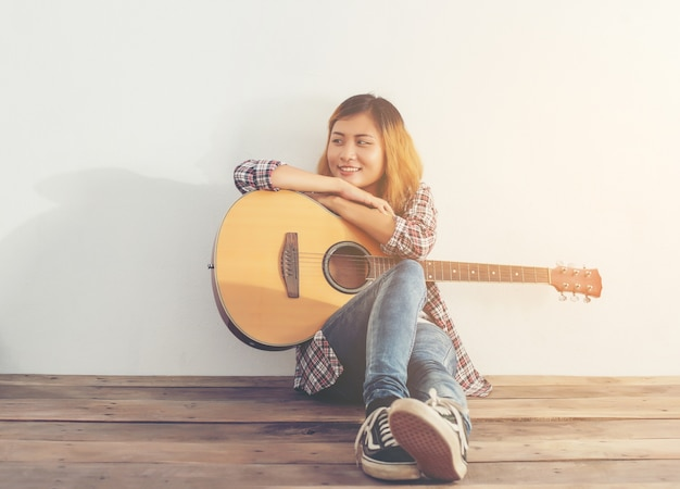Girl with a guitarr sitting on the floor
