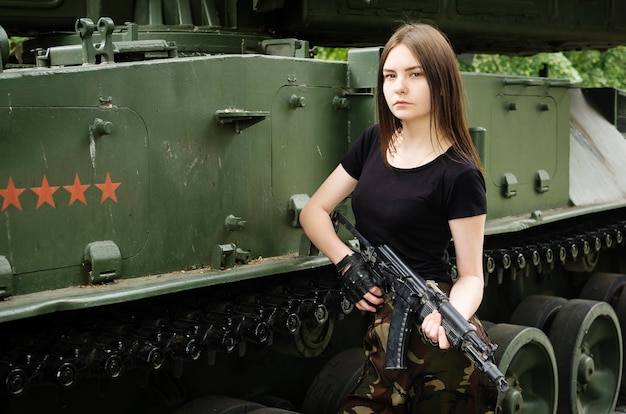 Girl with a gun near the armored vehicles