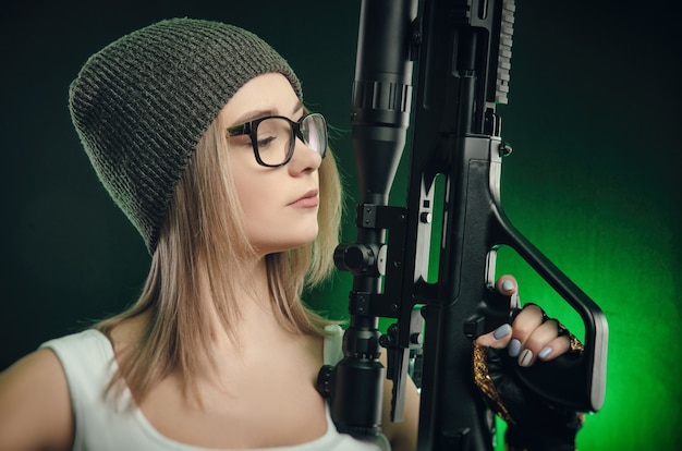 The girl with a gun posing on a black background ( sniper scope )