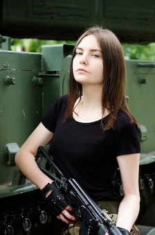 Girl with a gun standing near the armored cars